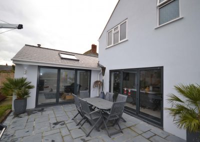 External rear view of completed single and two storey extensions creating ancillary accommodation showing multi fold doors and patio