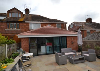External rear view of completed of single storey kitchen and dining room extension showing multi fold doors and patio
